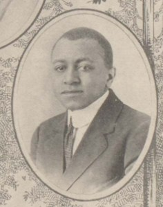 Black and white portrait photograph of a young African American male in a dark suit and a high white collar.