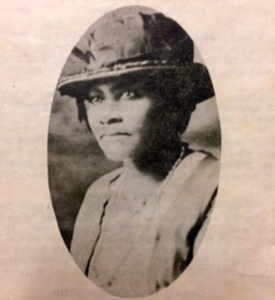 Black and white portrait photograph of an African American woman with a hat decorated with ribbons. She appears to be wearing a suit jacket and a string of pearls over a light-colored blouse.