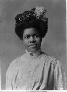 Black and white portrait photograph of an African American woman in a white lacy high-necked shirt. Her hair is piled on the top of her head, to which are attached silk flowers.