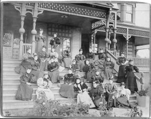 A group of women are seated on the steps of an ornate Victorian front porch. The women are dressed in clothing typical of the late 1800s, with puffy upper sleeves that taper into form-fitting lower arm coverage, corseted waists, and long skirts. All of the women are wearing some style of hat either decorated with flowers, or ribbons.