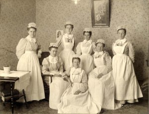 A group of women, some seated and some standing. All are wearing light-colored dresses with long white aprons over. All are also wearing ruffled white nurses caps, as well as ruffled collars.