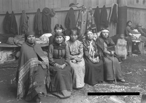 A group of middle-aged and elderly Native American women who are seated in a cedar longhouse. The women are dressed in non-Native attire, some with simple head wraps.