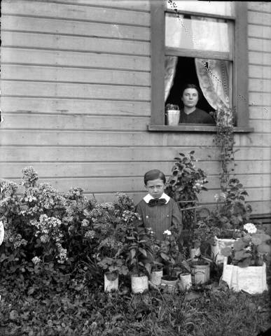 A child with a bowtie kneels in a garden patch behind small potted plants. Above him, in a window behind him, is a woman looking out at the photographer.