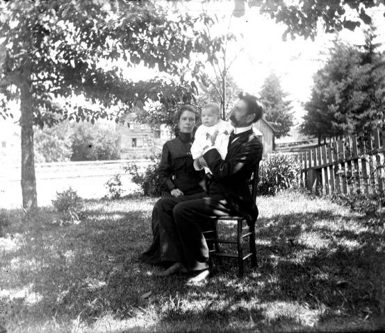 A woman, man, and baby sit in a yard. The man holds the baby up to face the camera. The day appears sunny and warm.
