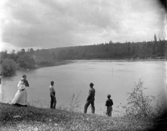 A woman in white holds a baby, three men stand with their backs turned to the camera. The group is overlooking a body of water, possibly a river.