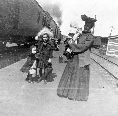 A woman in a large hat and long dress stands to the right holding a baby in white. Behind her to the left are a girl around 10 in a furry hood, and a toddler in what looks like a cape. They are holding hands. Behind them a train smokes, waiting to depart, or just arrived.