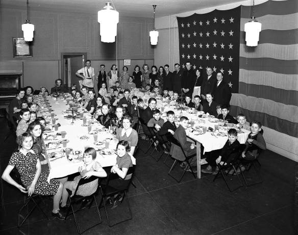 Two tables seat a group of children who appear to be dressed up. A line of women, and some men, are standing at the back of the room, looking over them. There is a large American flag covering one whole wall.