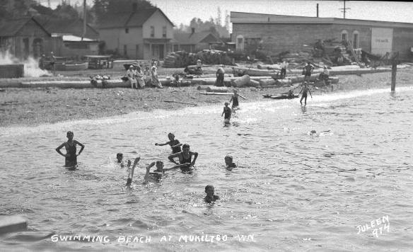 Children play in the shallows at a beach. In the background people sit on logs watching them. Behind them are some houses and a lot building.