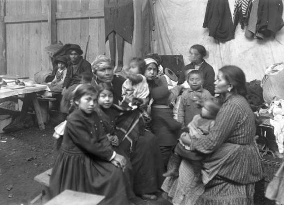 A group of children and women sit in a semi-circle inside a wooden building. Two in the group appear to be adults, the rest range from infant to perhaps preteen.