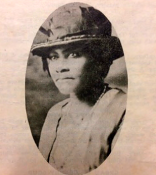 A portrait of a woman in a light-colored jacket, wearing a ribboned hat of similar color.