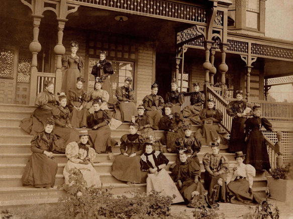 Sepia image of a group of women seated on the steps of an elaborate porch.