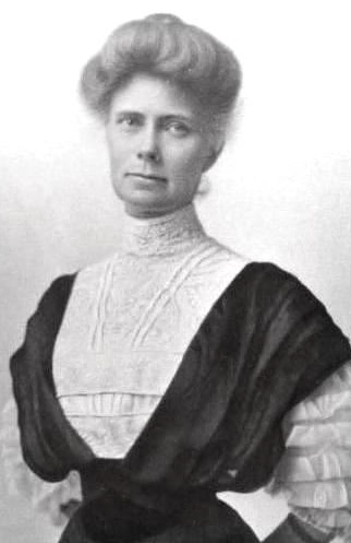 A woman with her hair piled into a bun, wearing a high-collared white dress with a sleeves.